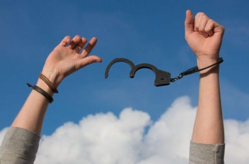 Metaphorical handcuffs breaking free of debt by means of debt consolidation